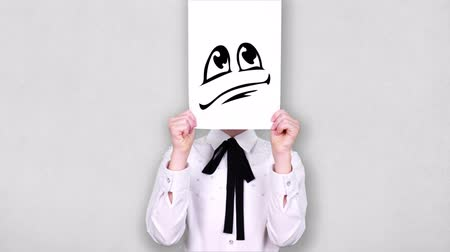 испуг : portrait, teenager holds white paper sheet with disappointed smiley drawing, animation, covering face. emotions, Imagination, creativity, successful idea concept.