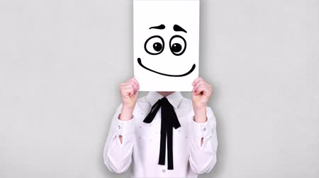 caricatura : portrait, teenager holds white paper sheet with confused smiley drawing, animation, covering face. emotions, Imagination, creativity, successful idea concept.