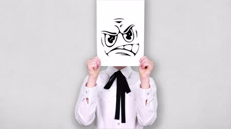 карикатура : portrait, teenager holds white paper sheet with furious smiley drawing, animation, covering face. emotions, Imagination, creativity, successful idea concept. Стоковые видеозаписи