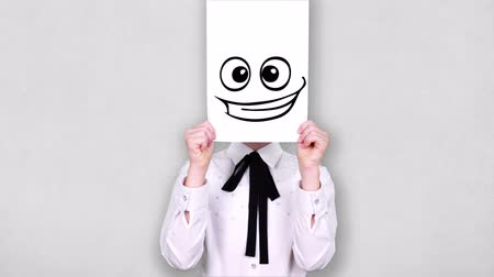 карикатура : portrait, teenager holds white paper sheet with excited smiley drawing, animation, covering face. emotions, Imagination, creativity, successful idea concept.