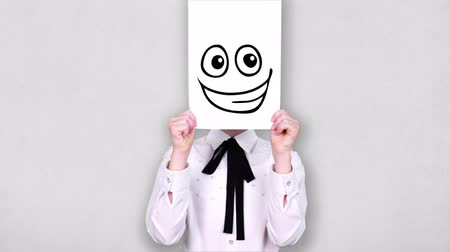 карикатура : portrait, teenager holds white paper sheet with silly smiley drawing, animation, covering face. emotions, Imagination, creativity, successful idea concept.