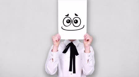 risonho : portrait, teenager holds white paper sheet with crazy smiley drawing, animation, covering face. emotions, Imagination, creativity, successful idea concept.