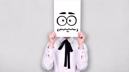 карикатура : portrait, teenager holds white paper sheet with nervous smiley drawing, animation, covering face. emotions, Imagination, creativity, successful idea concept.