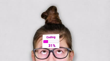 güncelleştirme : close-up, a smart teenager face, a child in glasses, with a sticker on his forehead. an animation of Coding process takes place on the sticker. Stok Video