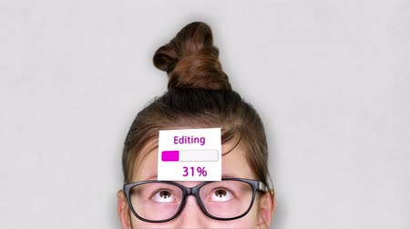 frissítést : close-up, a smart teenager face, a child in glasses, with a sticker on his forehead. an animation of Editing process takes place on the sticker. Stock mozgókép