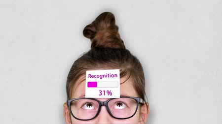 atualizar : close-up, a smart teenager face, a child in glasses, with a sticker on his forehead. an animation of Recognition process takes place on the sticker. Vídeos