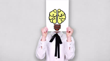 portrait, teenager holds white paper sheet with light bulb brain drawing, animation, in front of face. Imagination, creativity, successful idea concept. business , education Archivo de Video