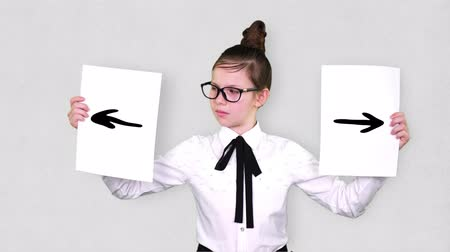 doubt : portrait, teenager girl holds two white paper sheets with arrows drawings, animations. concept of choice, you always need to choose between something.