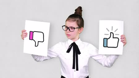 oportunidade : portrait, teenager girl holds two white paper sheets with like and dislike drawings, animations. concept of choice, you always need to choose between something. Stock Footage