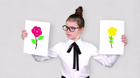 nejistota : portrait, teenager girl holds two white paper sheets with the flowers drawings, animations. concept of choice, you always need to choose between something.