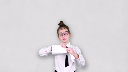 teenager girl angrily tears white sheets of paper into small pieces and throws them up.The girl wears glasses, is dressed like businesswoman. Concept of excessive temper at work..