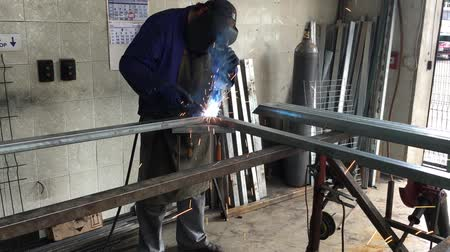 Man weld the frame of a fence in the garage. Sparks welding machine. Protective face mask.