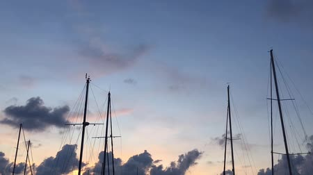 Timelapse: masts of sailing ships on a background of blue sky with clouds.