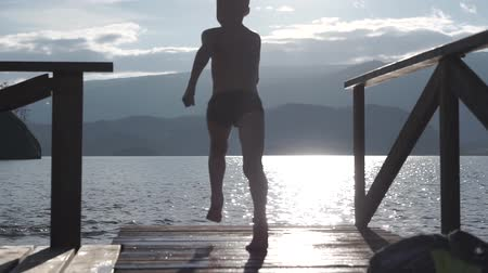delikanlı : Kid jumps off a wooden dock into the water.