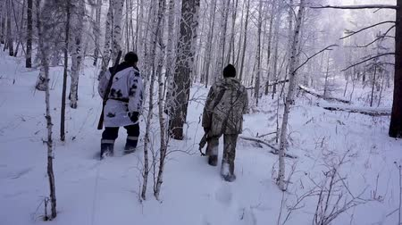 sniper scope : Two Hunters in the Woods. Armed Rangers in winter forest