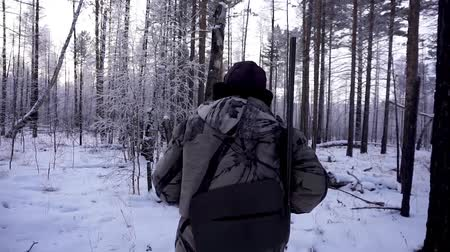 sniper scope : Hunters in the Woods. Armed Rangers in winter forest