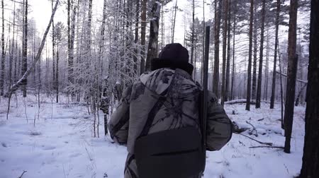 armed : Hunters in the Woods. Armed Rangers in winter forest