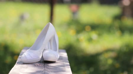 high heeled sandals : Wedding shoes on grass background Stock Footage