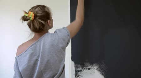 rolete : Girl paints wall with paint roller