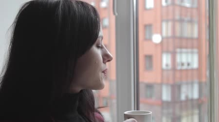 coffee time : girl enjoying drinking coffee and looking out of the window Stock Footage