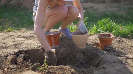 locsolás : Girl leaves soil in flower pots