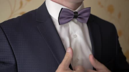 The groom straightens tie bow. Stock mozgókép
