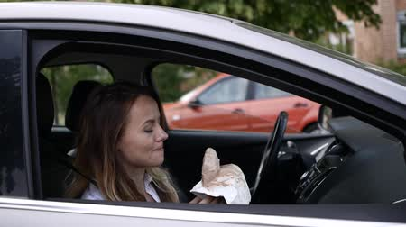 Young woman eats ice cream in the car Stock mozgókép