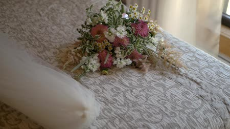 Wedding bouquet lies on bed