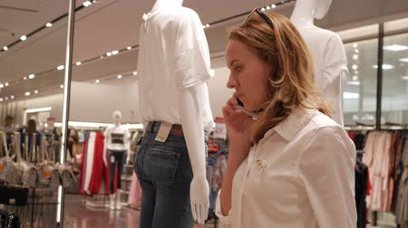 Girl talking on the phone in a clothing store Vídeos
