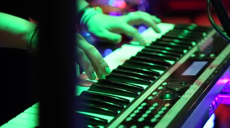munkaállomás : Female hands playing electric piano under colorful stage lighting, close-up.