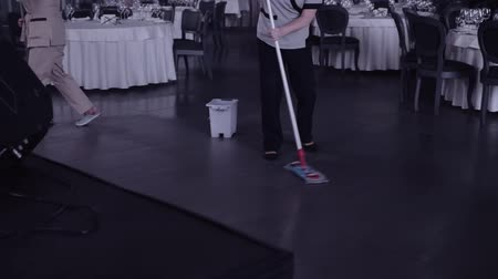 mopping : A woman with a MOP washes the floor in the restaurant