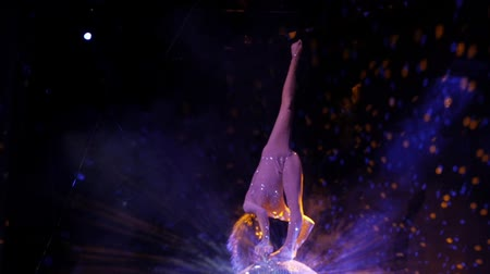 rhythmic : The gymnast performs an acrobatic number on a mirror ball