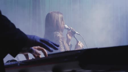protrude : The singer sings on stage to the accompaniment of the synthesizer Stock Footage