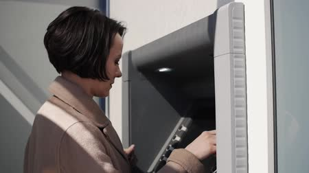 card pin : Woman dials the code on the ATM keyboard