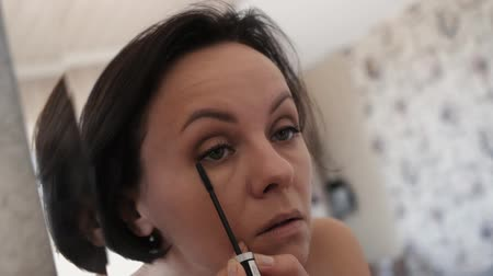 hůlky : A nice woman paints her eyelashes in front of a mirror.