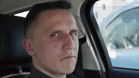 szemgolyó : Portrait of a man sitting in a car. He points his finger directly at the camera