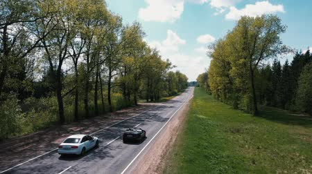 cabeçalho : The drone flies over the road between the trees and watching the cars