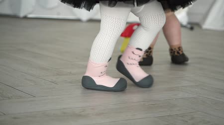 отношение : Children wear orthopedic shoes. Only their legs are visible