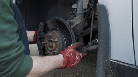 freio : The mechanic tries to remove the wheel drive to replace it