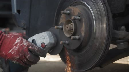 angle grinder : The mechanic cuts the wheel of the car with a grinder Stock Footage