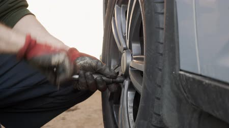 ремонтировать : The carmaker unscrews the wheel bolts to remove the wheel of the car.