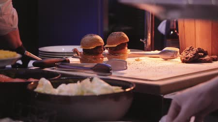 sajtburger : Cook prepares Burger in the restaurant