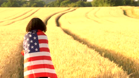 usa independence day : 4K video clip of mixed race African American girl teenager female young woman wrapped in an American US Stars and Stripes flag in a wheat field at sunset or sunrise Stock Footage