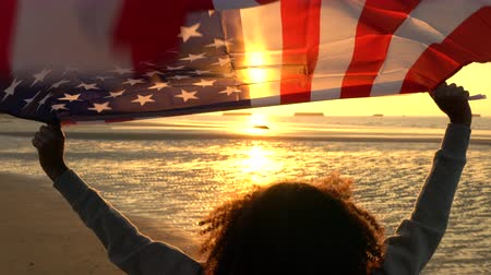usa independence day : Mixed race African American girl teenager female young woman holding an American US Stars and Stripes flag on a beach at sunset or sunrise Stock Footage