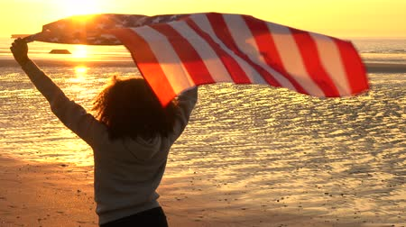tek başına : 4K jib crane video clip of mixed race African American girl teenager female young woman holding an American US Stars and Stripes flag on a beach at sunset or sunrise Stok Video