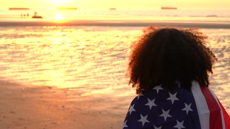 usa independence day : 4K video clip of mixed race African American girl teenager female young woman wrapped in an American US Stars and Stripes flag watching people having fun on a beach at sunset or sunrise