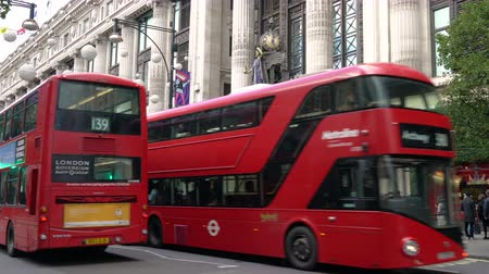 автобус : SELFRIDGES DEPARTMENT STORE, OXFORD STREET, LONDON, ENGLAND – 12 NOVEMBER 2017: 4K video of traffic, taxis and red double decker London buses driving past Selfridges, Oxford street, London, England