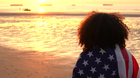 watching : 4K video clip of mixed race African American girl teenager female young woman wrapped in an American US Stars and Stripes flag, watching people playing on a beach at sunset or sunrise Stock Footage