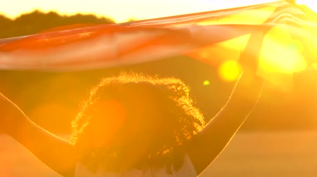 usa independence day : 4K video clip of mixed race African American girl teenager female young woman holding an American flag blowing in the wind at sunset or sunrise Stock Footage