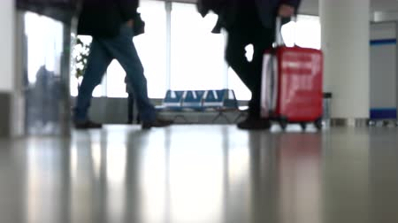 névtelen : 4K ground level video clip of anonymous people walking through an airport terminal with suitcases, bags and baggage Stock mozgókép